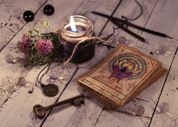 Black candle and old tarot cards on wooden planks. Halloween and fortune telling concept. Mystic background with occult and magic objects on witch table.
