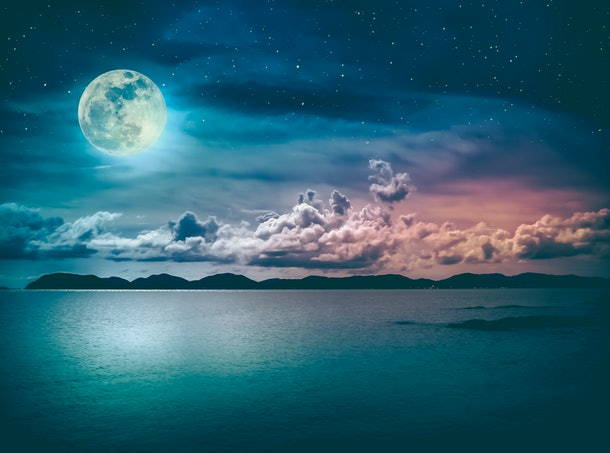 Beautiful landscape view of the sea with many stars . Attractive sky and  full moon on seascape to night. Serenity nature background. High contrast. The moon taken with my own camera.