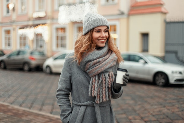 Happy young woman smiling in a trendy coat with a knitted vintage hat and fashionable warm scarf with a coffee walk in the city on a winter day