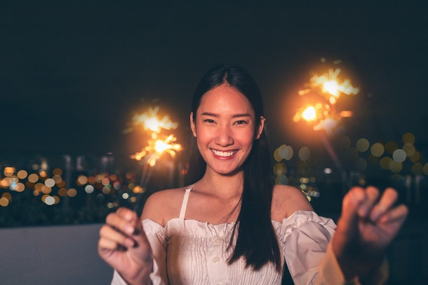 Beautiful young asian brunette woman with white dress joying Christmas or New Year night on a city.Woman holding sparkler against defocused lights, close up.