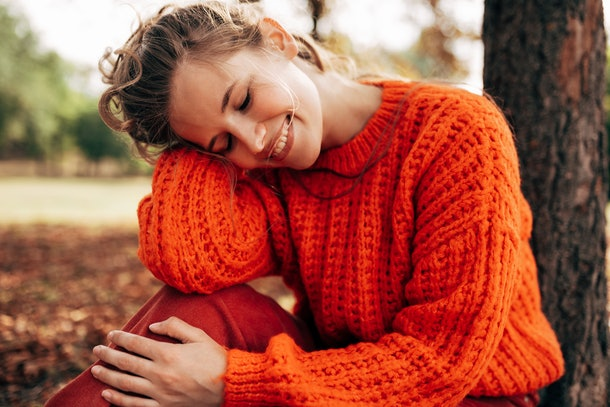 Outdoor image of a attractive young woman smiling, wearing orange knitted sweater posing on fall nature background. Beautiful female with closed eyes has dreamy expression, resting outdoor in the park