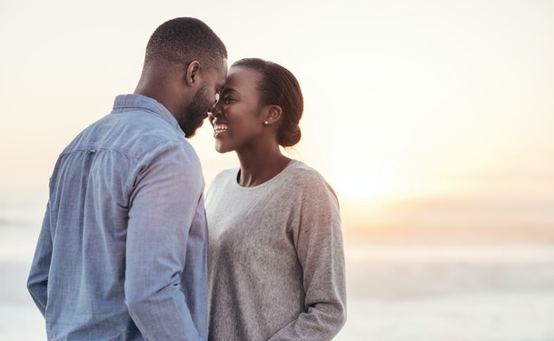 Smiling young African couple talking and laughing together while standing face to face on a beach at sunset