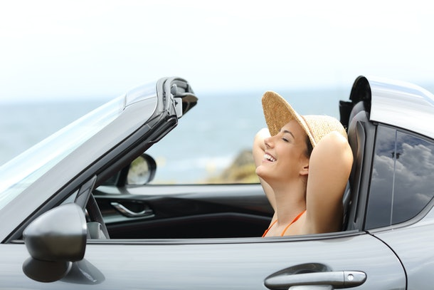 Side view portrait of a relaxed driver resting inside a convertible car on summer vacation