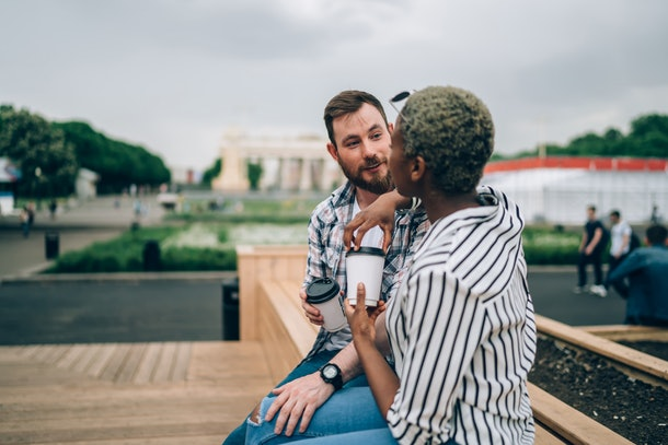 Side view of multiethnic couple with unrecognizable listening black girlfriend and talking boyfriend looking at each other sitting together with paper cups in park in cloudy weather