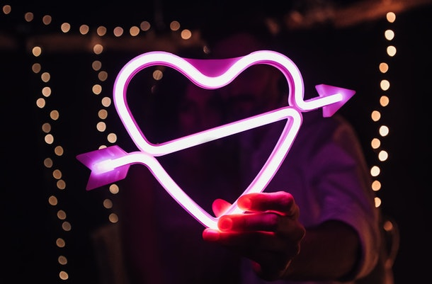 Glowing bright luminous neon heart sign pierced by cupid arrow, amour shape in vivid colors. Newlyweds holding digital shiny love target. Lovely young couple have a date, spending time together.